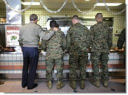 President George W. Bush stands in a chow line with Marines before sitting down for lunch with military personnel at Marine Corps Base Camp Pendleton, Calif., Tuesday, Dec. 7, 2004. White House photo by Eric Draper