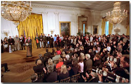 """President George W. Bush hosts a visit by the Champion NCAA teams to the East Room March 12. During their visit, the teams posed for pictures with the President and presented him with many team jerseys carrying such names as, """"Bush #1"""" and """"The Prez #1."""" White House photo by Paul Morse."""