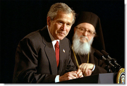 """Accompanied by His Eminence Archbishop Demetrios, Primate of Greek Orthodox Church of America, President George W. Bush addresses attendees of the Greek Independence Day Ceremony in the Eisenhower Executive Office Building March 25, 2002. """"America and Greece are strong allies, and we're strategic partners,"""" said President Bush. """"Our nation has been inspired by Greek ideals, and enriched by Greek immigrants."""" White House photo by Paul Morse."""