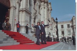 """President George W. Bush and Peruvian president Alejandro Toledo (right) wave from the steps of the Presidential Palace in Lima, Peru, March 23, 2002. """"It is an honor for me to be the first sitting President of the United States to visit Peru,"""" said President Bush during the two leaders' joint press conference where he explained that steps such as reintroducing the Peace Corps to Peru are being taken to strengthen the relationship between America and Peru."""
