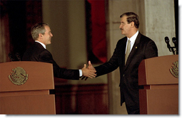 President George W. Bush reaches for Mexico's President Vicente Fox during a joint press conference at the Palacio de Gobierno in Monterey, Mexico, Friday, March 22.