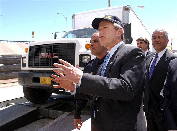 """President George W. Bush reviews the Vehicle and Cargo Inspection System during a tour of the cargo dock at the Bridge at the Americas in El Paso, Texas, Thursday, March 21. Also pictured, from left, are Port Operations Director David Longoria, Texas Governor Rick Perry and Congressman Henry Bonilla (R-23rd). """"I want this border to be modern; I want it to have the very best technology,"""" said the President upon his arrival at the El Paso airport. """"I don't want it to be a neglected part of our country. I want it to be a place where we spend a lot of time and focus on it, so that it works the best it can possibly work."""" White House photo by Eric Draper."""