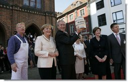 Standing with German Chancellor Angela Merkel, President George W. Bush holds up a ceremonial gift of a barrel of herring in Stralsund, Germany, Thursday, July 13, 2006. Mrs. Bush is pictured at the right.  White House photo by Eric Draper