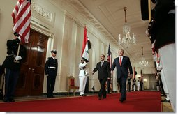 """President George W. Bush and Iraqi Prime Minister Nouri al-Maliki walk through the Cross Hall to the East Room where the two leaders held a joint press conference Tuesday, July 25, 2006. """"You have a strong partner in the United States of America, and I'm honored to stand here with you, Mr. Prime Minister,"""" said President Bush. """"It's a remarkable and historical moment, as far as I'm concerned, to welcome the freely elected leader of Iraq to the White House."""" White House photo by Kimberlee Hewitt"""