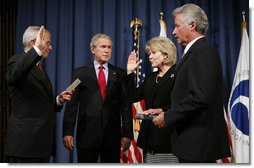 """President George W. Bush attends the ceremonial swearing-in of Mary Peters as the 15th U.S. Secretary of Transportation, Tuesday, Oct. 17, 2006 at the Department of Transportation in Washington, D.C., as White House Chief of Staff Josh Bolten administers the oath of office and Peter's husband, Terryl """"Terry"""" Peters, Sr. holds the bible.  White House photo by Paul Morse"""