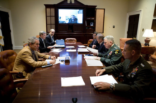President George W. Bush speaks during a video teleconference with Vice President Dick Cheney, on screen, and military commanders in the Roosevelt Room of the White House, Saturday, Oct. 21, 2006. Pictured from left are National Security Advisor Stephen Hadley, Deputy National Security Advisor J.D. Crouch, Senior Advisor to the Secretary of State on Iraq David Satterfield, Secretary of Defense Donald Rumsfeld, U.S. Army General John Abizaid and Chairman Joint Chiefs of Staff U.S. Marine General Peter Pace. White House photo by Eric Draper