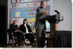 """President George W. Bush delivers remarks Wednesday, Oct. 18, 2006, on No Child Left Behind during a visit to the Waldo C. Falkener Elementary School in Greensboro, N.C. The President congratulated the school's principal, teachers and the parents for """"working hard to make this a fantastically interesting place for our children to go to school."""" Seated in the background are Secretary of Education Margaret Spellings and Dr. Amy Holcombe, Principal of the school.  White House photo by Paul Morse"""