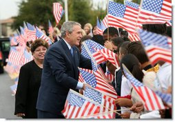 President George W. Bush reaches into a flurry of flags to greet students at George W. Bush Elementary School in Stockton, Calif., Tuesday, Oct. 3, 2006. White House photo by Eric Draper