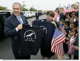 President George W. Bush holds up a T-shirt from George W. Bush Elementary School while visiting with students in Stockton, Calif., Tuesday, Oct. 3, 2006.  White House photo by Eric Draper