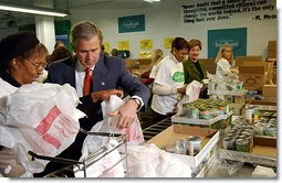 """President George W. Bush and Laura Bush help volunteers pack food during their visit to the Capital Area Food Bank in Washington, D.C., Thursday, Dec. 19. """"More Americans need to volunteer. There are ways to do so. The USAFreedomCorps.gov on the web page is the place to look,"""" said the President in his remarks. """"You can call 1-877-USA-CORPS and find out ways that you can help. If you are interested in being a part of feeding those who hunger, this is a great place to come to.""""  White House photo by Tina Hager"""