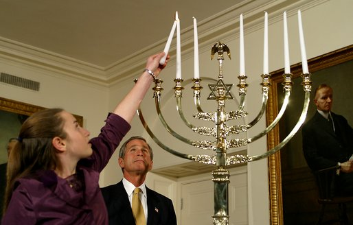 President George W. Bush watches as Daniella Wald, 12, lights one of the candles on the Menorah Wednesday, Dec 4 in the White House. President Bush presented one of the lighted candles to Daniella Wald, who lit the first three candles, and she presented the lighter candle to her sister, Alexandra Wald, 15, who lit the other three. Both of the girls are from Manhattan, and their father, Victor Wald, was killed in the Sept. 11 attacks on the World Trade Center. White House photo by Paul Morse.