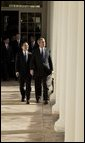"""After the Arrival Ceremony, President George W. Bush and Premier Wen Jiabao of China walk along the Rose Garden Colonnade on their way to the Oval Office Tuesday, Dec. 9, 2003. """"We're going to have extensive discussions today on a lot of issues,"""" said the President during an Oval Office meeting with the media. """"We've just had a very friendly and candid discussion. There's no question in my mind that when China and the United States works closely together we can accomplish a lot of very important objectives."""" White House photo by Paul Morse"""