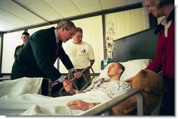 President George W. Bush speaks to U.S. Army Corporal James Rednour, of Ft. Campbell, Kentucky, after presenting him The Purple Heart for injuries Cpl. Rednour sustained while serving in Iraq. President Bush visited troops at Walter Reed Army Medical Center in Washinton, D.C., Thursday, December 18, 2003. Cpl. Rednour's parents, Chuck and Cindy look on.  White House photo by Eric Draper