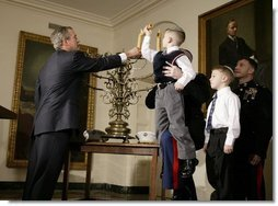 President George W. Bush helps Jacob Murphy light a menorah along with his father Captain Neil Murphy Jr. Wednesday afternoon December 22, 2003 at the White House.  White House photo by Paul Morse