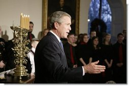 President George W. Bush comments to the press after lighting a menorah Wednesday afternoon December 22, 2003 at the White House.  White House photo by Paul Morse
