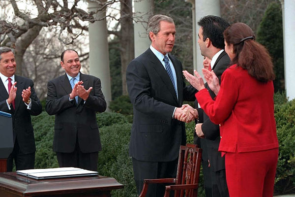 President George W. Bush signs papers with Latino leaders during a ceremony transmitting his tax cut proposal to Congress in the Rose Garden of the White House
