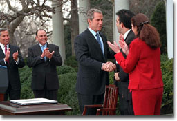 President George W. Bush signs papers with Latino leaders during a ceremony transmitting his tax cut proposal to Congress in the Rose Garden of the White House on Thursday February 8, 2001 (WHITE HOUSE PHOTO/DAVID SCULL)
