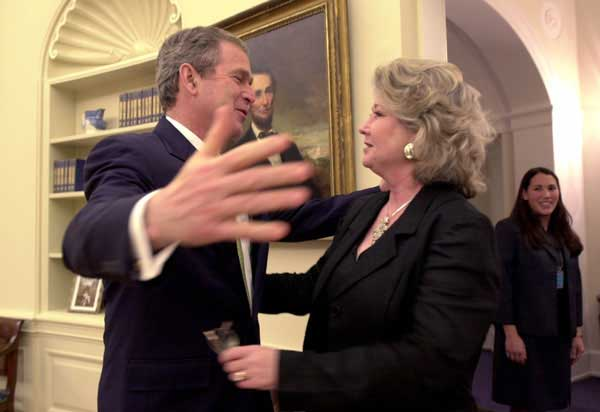 President George W. Bush hugs Katha Black, National PTA Outstanding Teacher of the Year during an oval office visit, Thursday, March 15. Also pictured is White House Staffer Anne Trenolone, at right.