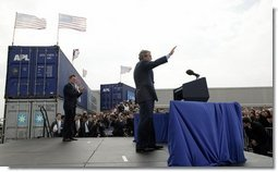 As Homeland Security Secretary Tom Ridge stands nearby, President George W. Bush waves to the audience after delivering remarks on homeland security at the Port of Charleston, S.C., Feb. 5, 2004.  White House photo by Paul Morse