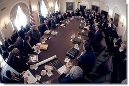 Seen through a fish-eye lens, President George W. Bush talks with reporters during a Cabinet Meeting at the White House Monday, Feb. 2, 2004.  White House photo by Eric Draper