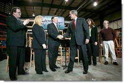 President George W. Bush greets the stage participants at the end a conversation on the economy at SRC Automotive in Springfield, Mo., Monday, Feb. 9, 2004. From left, they are Mike Sadler, President of Custom Manufacturing and Polishing; Tricia Derges, CEO of Mostly Memories; Jack Stack CEO of SRC Automotive; Teresa Noblitt, SRC Automotive accountant; and Gary Brown, SRC Automotive Warehouse Supervisor.  White House photo by Eric Draper