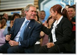 President George W. Bush and accounting clerk Neomi Gonzalez react on stage during a conversation on the economy with employees at Nu-Air Manufacturing Company in Tampa, Florida, Monday, Feb. 16, 2004.  White House photo by Eric Draper