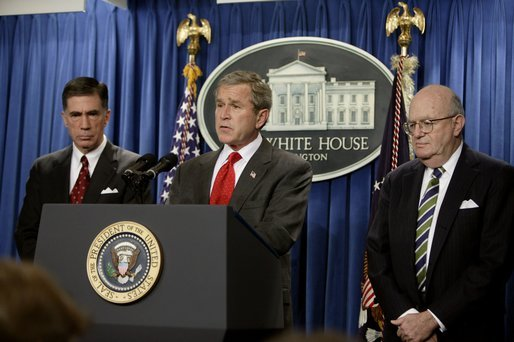 """President George W. Bush holds a press briefing at the White House Friday, Feb. 6, 2004. """"Today, by executive order, I am creating an independent commission, chaired by Governor and former Senator Chuck Robb (left), Judge Laurence Silberman (right), to look at American intelligence capabilities, especially our intelligence about weapons of mass destruction,"""" said the President. White House photo by Paul Morse"""