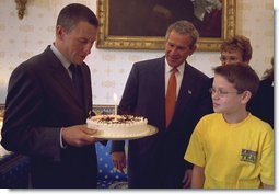President George W. Bush and Matthew Skowronski, 13, a leukemia survivor, (right), admire the cake Lance Armstrong was given by the White House in honor of his 31st birthday. Armstrong, a cancer survivor and 4-time winner of the Tour De France, spoke Wednesday, Sept. 18, to encourage and support new cancer survivorship initiatives and legislation. White House photo by Paul Morse.