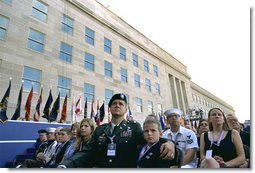 """Sitting in front of the rebuilt section of the Pentagon, service personnel and families listen to President George W. Bush at the Pentagon Observance Wednesday, Sept. 11. """"One year ago, men and women and children were killed here because they were Americans. And because this place is a symbol to the world of our country's might and resolve,"""" said the President. """"Today, we remember each life. We rededicate this proud symbol and we renew our commitment to win the war that began here."""" White House photo by Eric Draper."""