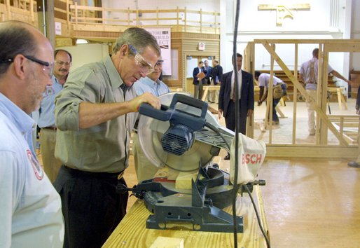 President George W. Bush takes a turn at a table saw during a Labor Day tour of the Carpenters Joint Apprenticeship Center on Neville Island, Pennsylvania. White House photo by Paul Morse.