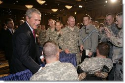 """President George W. Bush is greeted by military personnel following his address on the global war on terror at the Military Officers Association of America meeting Tuesday, Sept. 5, 2006, at the Capital Hilton Hotel in Washington. President Bush spoke about the U.S. and allies strategy for combating terrorism saying """"we're confronting them before they gain the capacity to inflict unspeakable damage on the world, and we're confronting their hateful ideology before it fully takes root."""" White House photo by Kimberlee Hewitt"""