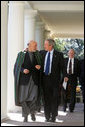 President George W. Bush walks with President Hamid Karzai of the Islamic Republic of Afghanistan along the colonnade in the Rose Garden Tuesday, Sept. 26, 2006. White House photo by David Bohrer