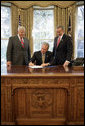 President George W. Bush signs S. 418, The Military Personnel Financial Services Protection Act, in the Oval Office Friday, Sept. 29, 2006. Standing with President Bush are bill sponsors Senator Mike Enzi, R-Wyo., left and Representative Geoff Davis, R-Ky. The legislation protects America's armed forces by banning unscrupulous companies from military bases. It also prohibits the selling of life insurance products military personnel and their dependents unless specified written disclosures have been provided. White House photo by Eric Draper