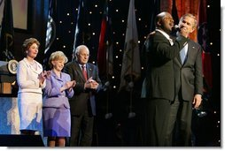 President George W. Bush puts his arm around Singer Bebe Winans as he sings 'God Bless America' during the 'Saluting Those Who Serve' event at the MCI Center in Washington, D.C., Tuesday, Jan. 18, 2005. Also pictured are, from left, Laura Bush, Lynne Cheney, and Vice President Dick Cheney.   White House photo by David Bohrer
