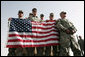 U.S. troops hold the American flag as they await Vice President Dick Cheney's arrival to a rally Tuesday, March 18, 2008 at Balad Air Base, Iraq. White House photo by David Bohrer