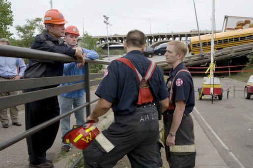 President George W. Bush, accompanied by Gary Babineau of Blaine, Minn., right, talks with fire and rescue personnel during a tour of the Interstate 35W bridge collapse scene in Minneapolis, Saturday, Aug. 4, 2007. Babineau, who was on the bridge during the collapse, helped rescue schoolchildren from their bus, seen in background, to safety. White House photo by Chris Greenberg