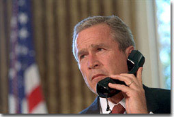 """Pledging support for New York, President George Bush talks with Governor George Pataki and Mayor Rudolph Giuliani in a televised telephone conversation from the Oval Office Sept. 13. """"Mr. President, you would be proud of the leadership and the cooperation we've seen here,"""" said the governor. White House photo by Eric Draper."""