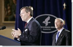 Mike Leavitt, newly sworn-in Secretary of Health and Human Services, addresses the audience after receiving the oath of office during ceremonies Friday, Feb.11, 2005, in the Great Hall at the U.S. Department of Health and Human Services. President George W. Bush looks on after introducing Secretary Leavitt.  White House photo by Paul Morse