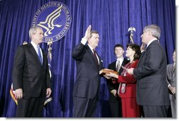 As President George W. Bush looks on, Mike Leavitt is sworn into office as Secretary of Health and Human Services by Chief of Staff Andrew Card. With Mr. Leavitt are his wife, Jackie, and son, Westin. The ceremony took place in the Great Hall at the U.S. Department of Health and Human Services.  White House photo by Paul Morse
