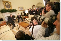 Surrounded by the members of the media, President George W. Bush greets Poland's President Aleksander Kwasniewski in the Oval Office Wednesday, Feb. 9, 2005.  White House photo by Eric Draper