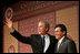 El Presidente George W. Bush, de lado del Fiscal General Alberto Gonzáles, agradece los aplausos después de dirigirse a la Hispanic Chamber of Commerce Legislative Conference el miércoles 20 de abril de 2005 en Washington, D.C.