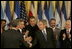 El Presidente George W. Bush estrecha la mano de legisladores, funcionarios del gobierno e invitados el martes, 2 de agosto de 2005 en el East Room de la Casa Blanca después de la ceremonia de promulgación de la CAFTA Implementation Act.