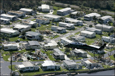 """Flying aboard Marine One, President George W. Bush surveys the damage from Hurricane Charley in Fort Myers, Fla., Aug. 15, 2004. Hurricane Charley made landfall Aug. 13. Throughout the next several three more storms would make landfall: Hurricane Frances on Sept. 5, Hurricane Ivan on Sept. 15, and Hurricane Jeanne on Sept 26. """"It's been a devastating period for the state of Florida. It is the first time in nearly 120 years that four hurricanes have hit the same state in a single season,"""" said the President during a visit to the region Sept. 29."""""""
