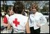 """Laura Bush speaks with American Red Cross Disaster Relief workers at the Vero Beach Community Center where disaster relief is offered to local residents Oct. 1, 2004. Vero Beach, Fla., was one of the areas hardest hit by Hurricanes Jeanne and Frances. """"See, these volunteers show the true heart of America, because we're a compassionate people, we care when a neighbor hurts, we long to help somebody when help is needed,"""" said President Bush during a visit with volunteers in Stuart, Fla., Sept. 30. """"They have the gratitude of all they've served, and they have the admiration for our whole country."""""""