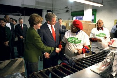 """President George W. Bush and Laura Bush help volunteers pack food during their visit to the Capital Area Food Bank in Washington, D.C., Thursday, Dec. 19. """"More Americans need to volunteer. There are ways to do so. The USAFreedomCorps.gov on the web page is the place to look,"""" said the President in his remarks. """"You can call 1-877-USA-CORPS and find out ways that you can help. If you are interested in being a part of feeding those who hunger, this is a great place to come to."""""""