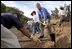 Working alongside volunteers, President George W. Bush lends a hand in repairing the Old Boney Trail at the Santa Monica Mountains National Recreation Area in Thousand Oaks, Calif., Aug. 15, 2003.