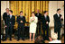 """Mrs. Laura Bush stands with members of the cast from the Tony award-winning musical """"Jersey Boys"""" as they perform during a luncheon for Senate Spouses in the East Room, Monday, June 12, 2006. White House photo by Shealah Craighead"""