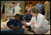 Laura Bush visits with a young boy displaced by Hurricane Katrina in the Cajundome at the University of Louisiana in Lafayette, La., Friday, Sept. 2, 2005.