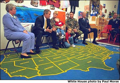 Photograph of the President with children. A map of the United States is on the carpet. White House photo by Paul Morse.