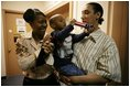 """Kevion Thigpen, 3, held by his parents Kanyatta """"Ken"""" Thigpen and his girlfriend Jewell Reed plays with a kaleidescope given to him by Laura Bush during a visit to the Rosalie Manor Community and Family Services center in Milwaukee, Wis., Tuesday, March 8, 2005. Citing a New York Times article by Jason DeParle Mrs. Bush credits Mr. Thigpen's determination to be a responsible father with bringing her attention to the needs of boys and young men."""